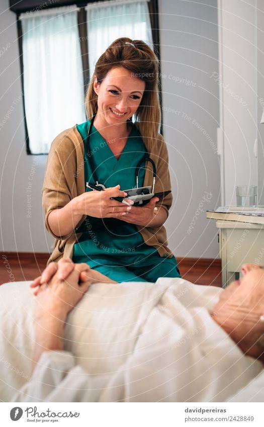 Ärztin tröstet ältere Patientin Krankheit Medikament Haus Arzt Krankenhaus sprechen Mensch Frau Erwachsene alt Lächeln authentisch Freundlichkeit Vertrauen