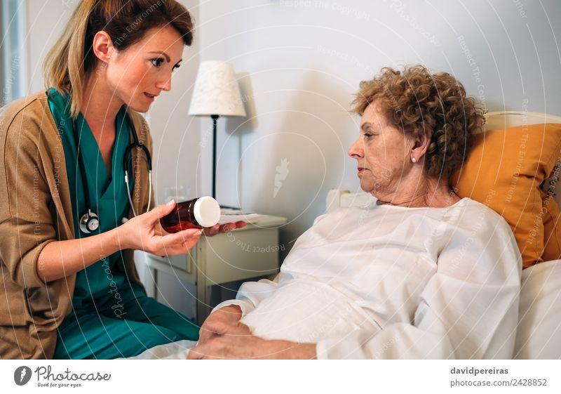 Ärztin erklärt Posologie Gesundheitswesen Behandlung Krankheit Medikament Haus Lampe Stuhl Arzt Krankenhaus Mensch Frau Erwachsene alt authentisch Versicherung