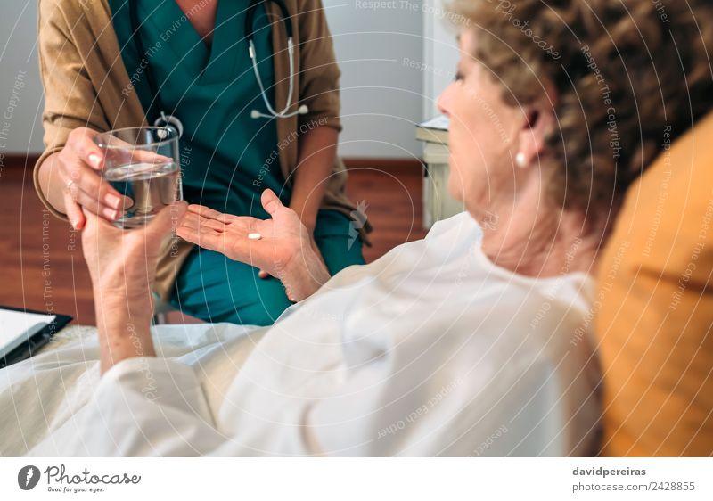 Ärztin gibt älteren Patienten Medikamente Gesundheitswesen Behandlung Krankheit Haus Arzt Krankenhaus Mensch Frau Erwachsene alt authentisch Geben Tablette