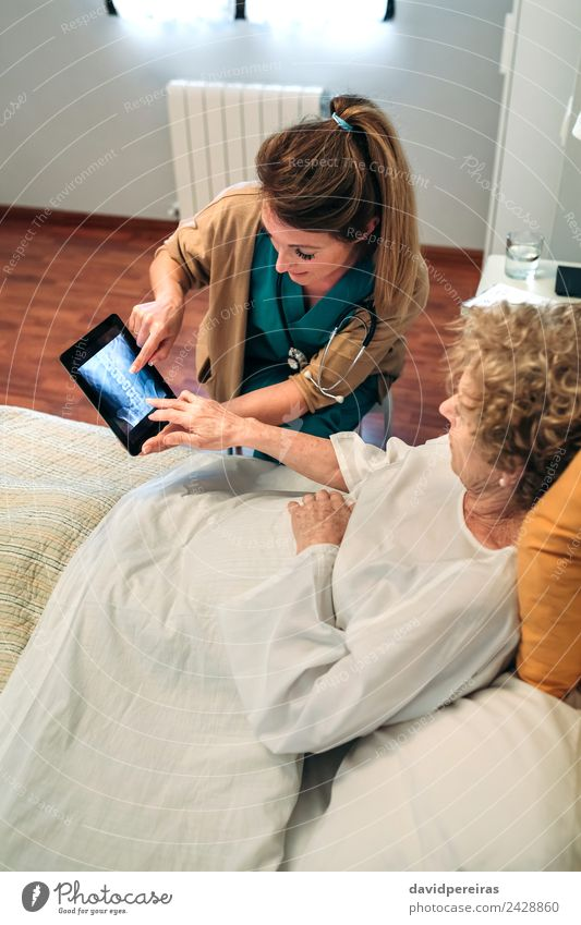 Ärztin, die ein Röntgenbild auf der Tablette zeigt. Krankheit Medikament Arzt Krankenhaus Mensch Frau Erwachsene alt authentisch Senior geduldig Knochenscan