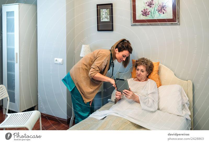 Frau Mensch alt Erwachsene Aussicht authentisch Information Stuhl Krankheit Medikament zeigen Arzt reif Krankenhaus vertikal Tablet Computer