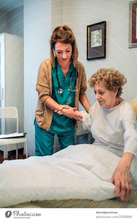 Betreuerin hilft älteren Patienten beim Aufstehen aus dem Bett Lifestyle Gesundheitswesen Krankheit Medikament Arzt Krankenhaus Mensch Frau Erwachsene alt