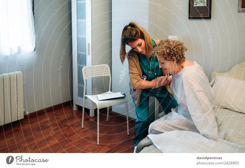 Betreuerin hilft älteren Patienten beim Aufstehen aus dem Bett Lifestyle Gesundheitswesen Krankheit Medikament Stuhl Arzt Krankenhaus Mensch Frau Erwachsene alt