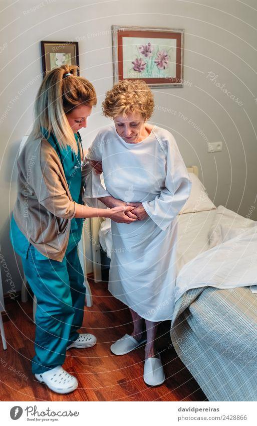 Betreuerin hilft älteren Patienten beim Aufstehen Lifestyle Gesundheitswesen Krankheit Medikament Arzt Krankenhaus Mensch Frau Erwachsene alt authentisch