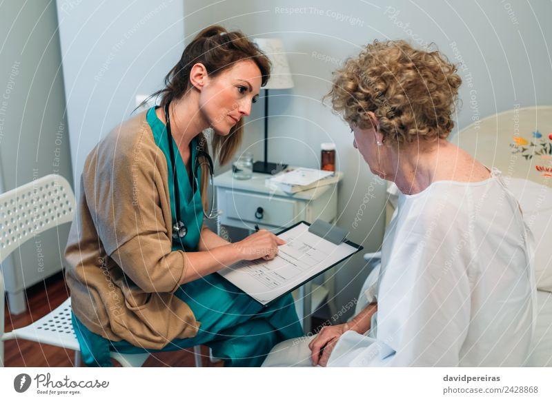 Ärztin beim Ausfüllen eines Fragebogens Gesundheitswesen Behandlung Krankheit Medikament Lampe Stuhl Arzt Krankenhaus Mensch Frau Erwachsene alt sitzen