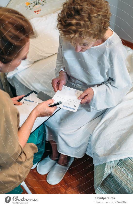 Arzt, der dem älteren Patienten ein Rezept ausstellt. Gesundheitswesen Behandlung Krankheit Medikament Krankenhaus Mensch Frau Erwachsene Hausschuhe alt sitzen