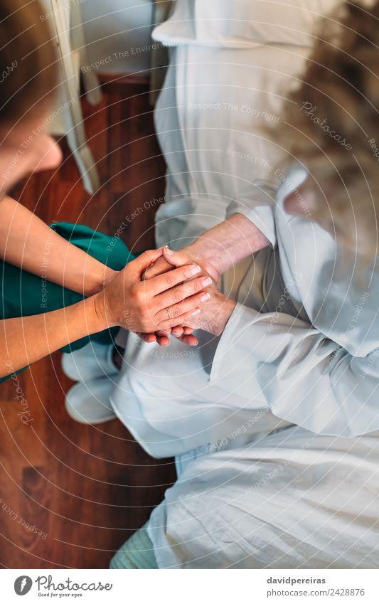 Ärztin hält Hand des Patienten Krankheit Medikament Arzt Krankenhaus Mensch Frau Erwachsene Fluggerät Hausschuhe alt authentisch Freundlichkeit Mitgefühl