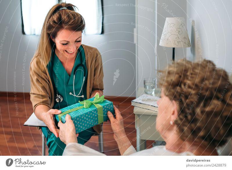 Ältere Patientin, die ihrem Arzt ein Geschenk macht. Glück Behandlung Krankheit Medikament Erholung Krankenhaus Mensch Frau Erwachsene alt Lächeln authentisch
