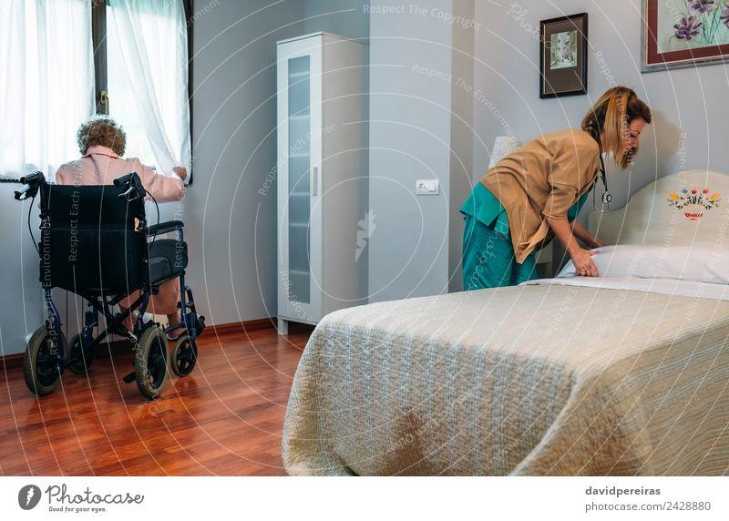 Betreuerin, die das Bett eines älteren Patienten anfertigt. Lifestyle Gesundheitswesen Krankheit Medikament Erholung Stuhl Schlafzimmer Arzt Krankenhaus Mensch