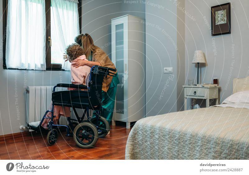 Betreuer mit einem älteren Patienten im Rollstuhl vor dem Fenster Lifestyle Gesundheitswesen Krankheit Medikament Arzt Krankenhaus Mensch Frau Erwachsene