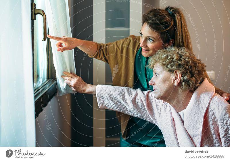 Betreuerin, die älteren Patienten den Blick durch das Fenster zeigt. Lifestyle Gesundheitswesen Krankheit Medikament Arzt Krankenhaus Mensch Frau Erwachsene alt