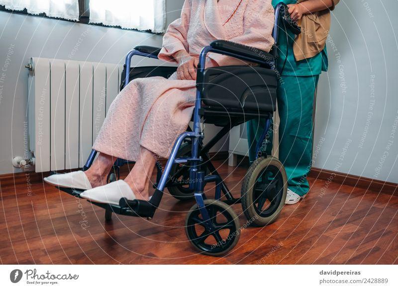 Arzt, der ältere Patienten im Rollstuhl trägt. Gesundheitswesen Krankheit Erholung Krankenhaus Mensch Frau Erwachsene Hausschuhe alt tragen authentisch