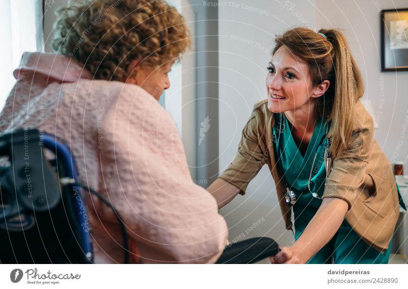Weibliche Ärztin im Gespräch mit älterem Patienten im Rollstuhl Gesundheitswesen Krankheit Erholung Arzt Krankenhaus sprechen Mensch Frau Erwachsene alt