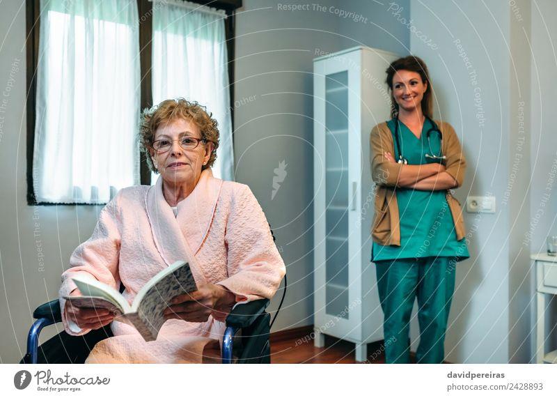 Älterer Patient posiert mit Arzt im Hintergrund Gesundheitswesen Krankheit Erholung lesen Schlafzimmer Krankenhaus Mensch Frau Erwachsene Buch alt Lächeln