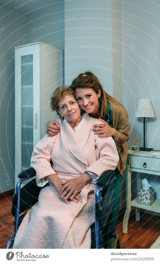 Weibliche Betreuerin posiert mit älterer Patientin schön Gesundheitswesen Krankheit Lampe Schlafzimmer Arzt Krankenhaus Mensch Frau Erwachsene alt Lächeln