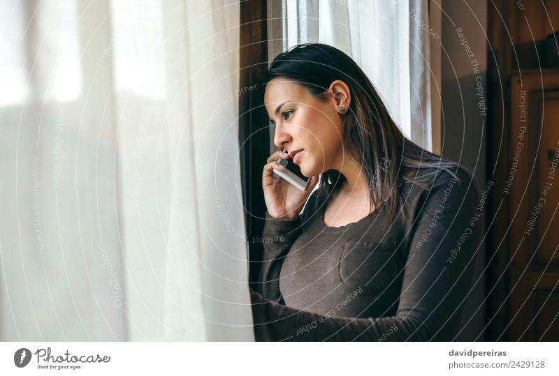 Frau spricht Handy und Schaufenster. Lifestyle schön sprechen Telefon PDA Mensch Erwachsene Traurigkeit warten authentisch modern niedlich traurig ernst Fenster