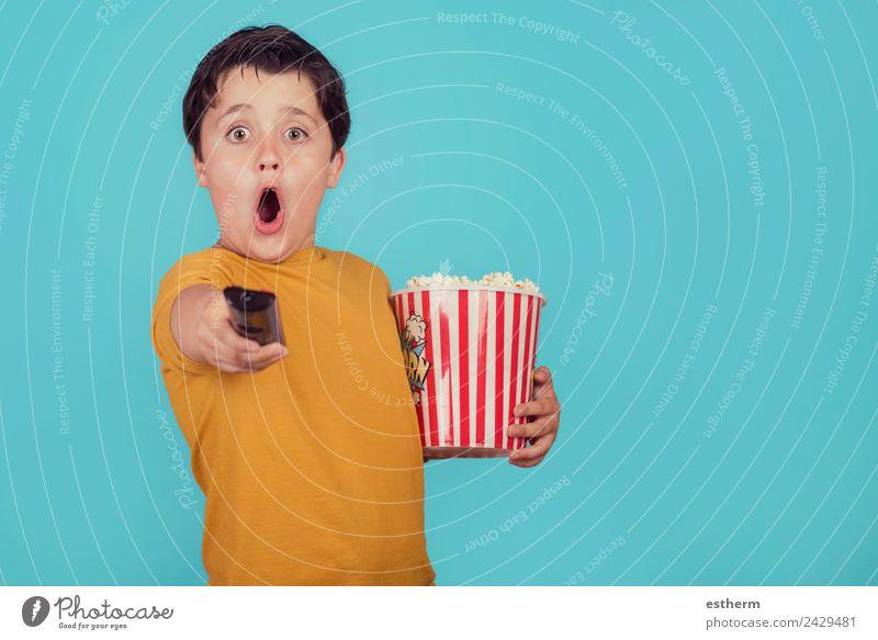überraschter Junge mit Popcorn und Fernseher-Fernbedienung Lebensmittel Ernährung Fastfood Lifestyle Freude Freizeit & Hobby Mensch maskulin Kind Kleinkind