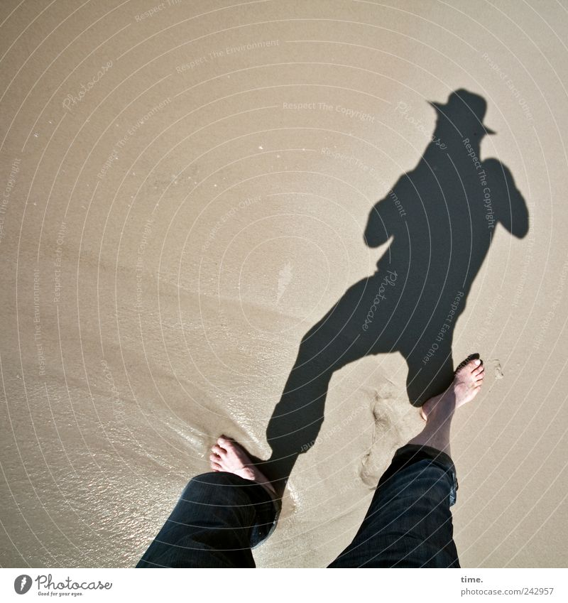 Schattenknipser Strand maskulin Mann Erwachsene Beine Fuß Sand Wasser Hose Hut nass Barfuß feucht Farbfoto Gedeckte Farben Außenaufnahme Textfreiraum links