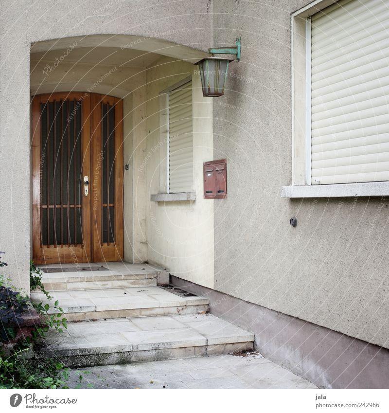 verreist Pflanze Sträucher Grünpflanze Haus Einfamilienhaus Bauwerk Gebäude Architektur Mauer Wand Treppe Fassade Fenster Tür Briefkasten Laterne alt trist