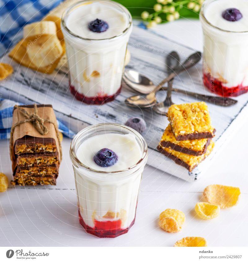 Joghurt im Klarglas Milcherzeugnisse Marmelade Ernährung Frühstück Diät Getränk Erfrischungsgetränk Löffel Tisch Blume Holz natürlich oben blau weiß Tradition