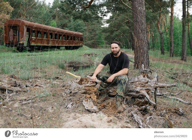 bärtiger Holzfäller mit einer Axt, die neben einem rostigen Zug sitzt. Mensch maskulin Junger Mann Jugendliche Erwachsene Haare & Frisuren Gesicht Auge Nase