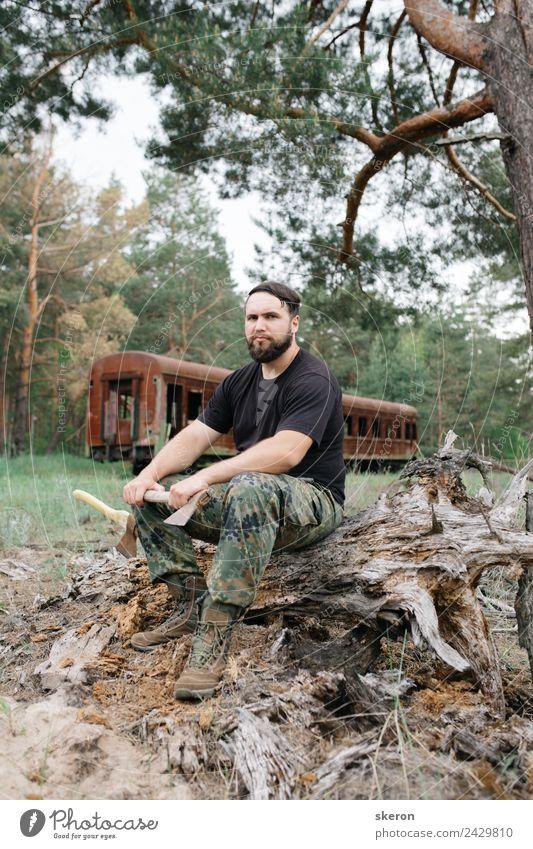 bärtiger Jäger, der auf der Wurzel eines trockenen Baumes sitzt. Lifestyle Freizeit & Hobby Ferien & Urlaub & Reisen Tourismus Abenteuer Mensch maskulin Mann