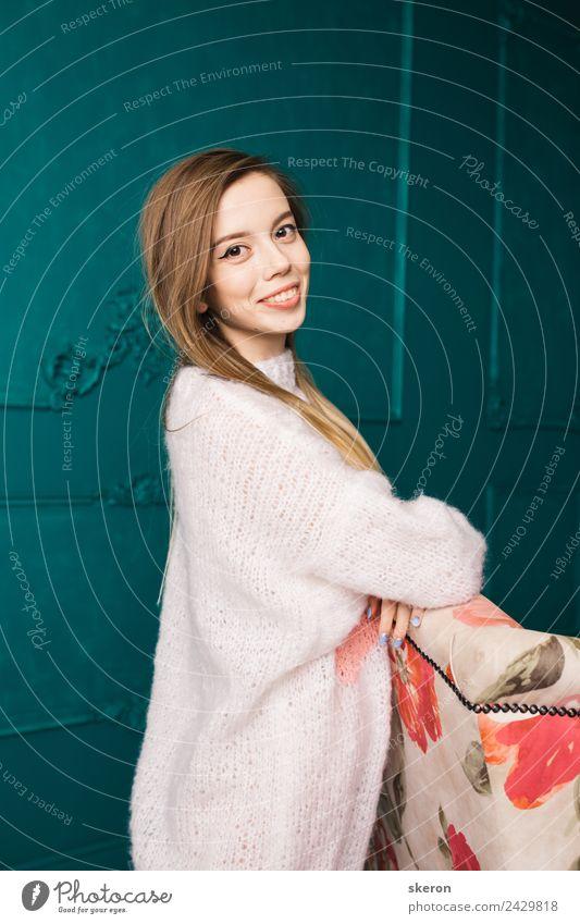 lächelndes Mädchen in einem langen Pullover steht neben dem Stuhl elegant Stil Design schön Wellness harmonisch Zufriedenheit Freizeit & Hobby Diät Erfolg grün
