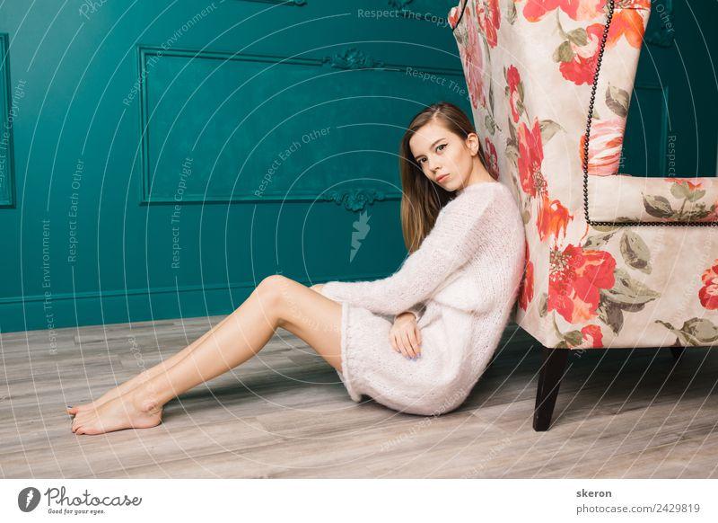 Mädchen mit langen Haaren und schlanken Beinen, die in der Nähe des Stuhls sitzen. Mensch feminin Junge Frau Jugendliche Erwachsene Körper Haut Haare & Frisuren