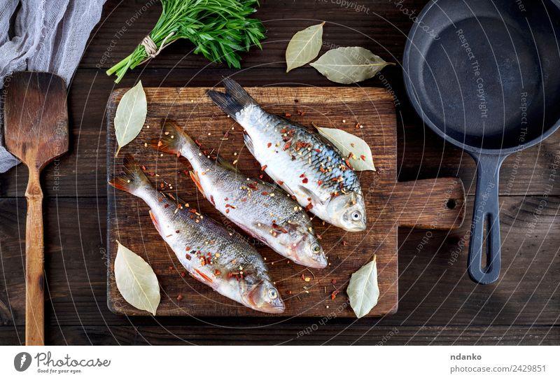 Fisch auf einem braunen Holzbrett Meeresfrüchte Kräuter & Gewürze Ernährung Abendessen Diät Pfanne Tisch Tier Fluss dunkel frisch oben retro schwarz Barsch