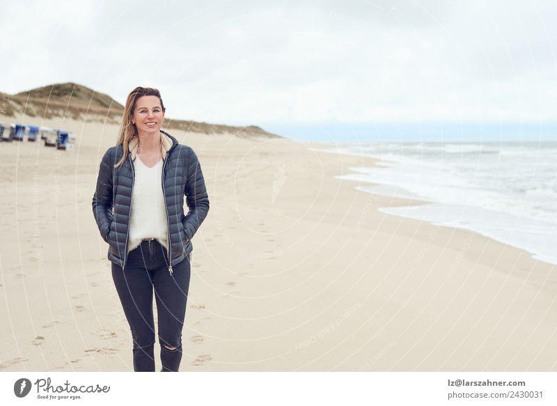 Frau, die an einem bewölkten Tag am Strand spazieren geht. Freizeit & Hobby Freiheit Meer Erwachsene 1 Mensch 45-60 Jahre Sand Wolken Herbst Küste Nordsee