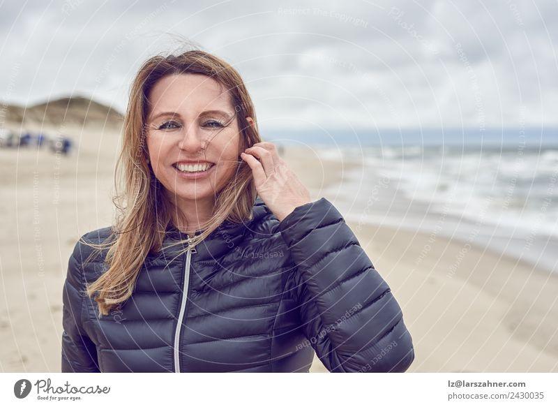 Attraktive Frau an einem windgepeitschten Strand Gesicht Freizeit & Hobby Freiheit Meer Erwachsene 1 Mensch 45-60 Jahre Sand Wolken Herbst Unwetter Wind Küste