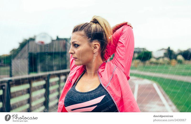 Junge Frau, die die Arme streckt, bevor sie im Freien trainiert. Lifestyle Sport Joggen Rennbahn Mensch Erwachsene Park Straße blond Zopf Linie Fitness