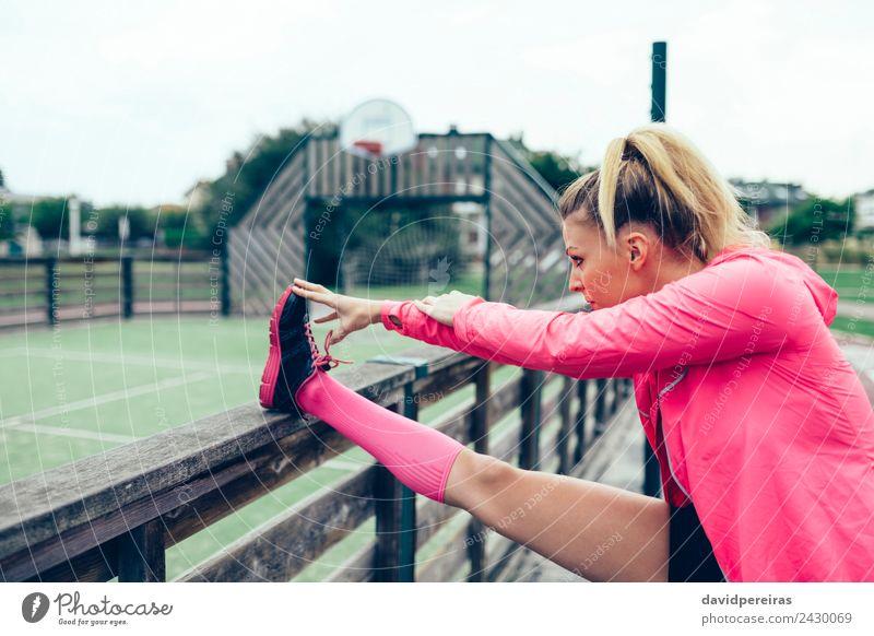Junge Frau, die vor dem Training im Freien die Beine streckt. Lifestyle Sport Joggen Rennbahn Mensch Erwachsene Arme Park Straße Turnschuh blond Zopf Linie