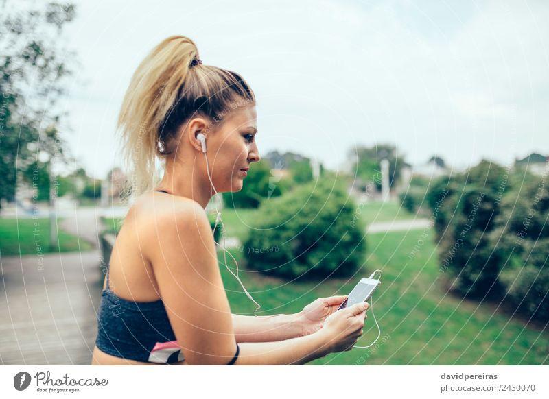 Frau mit Kopfhörer, die Musik auf dem Smartphone hört. Lifestyle schön Sport Joggen Telefon PDA Technik & Technologie Mensch Erwachsene Hand Natur Park blond