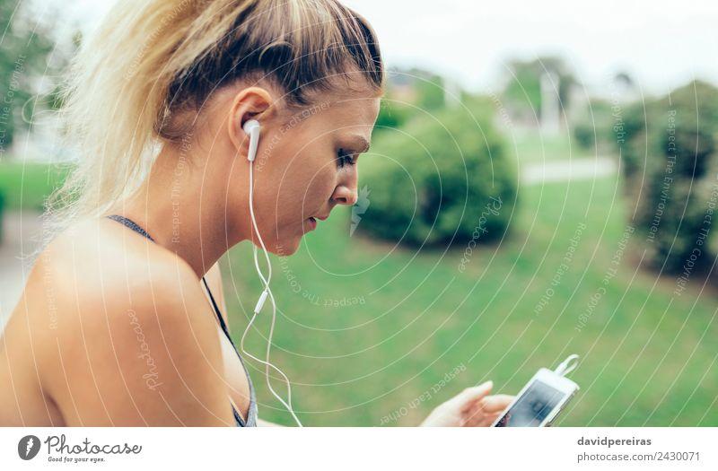 Frau mit Kopfhörer, die Musik auf dem Smartphone hört. Lifestyle Sport Joggen Telefon PDA Technik & Technologie Mensch Erwachsene Hand Park blond Zopf Fitness
