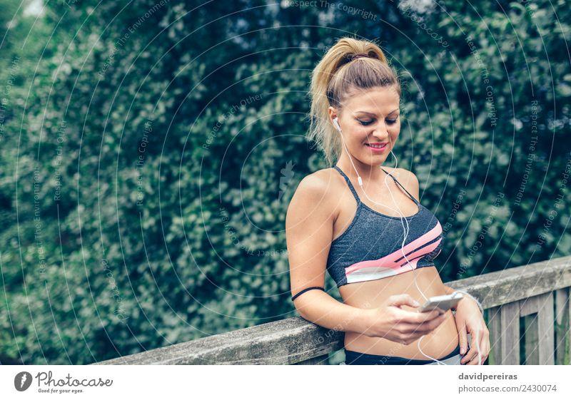 Frau in Sportbekleidung mit Kopfhörern, die wie ein Smartphone aussehen. Lifestyle Freude Glück Musik Telefon PDA Technik & Technologie Mensch Erwachsene Hand