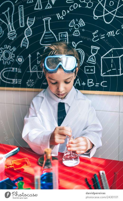 Ernsthaftes Kind beim Spielen mit chemischen Flüssigkeiten Flasche Glück Wohnung Tisch Wissenschaften Klassenraum Tafel Labor Mensch Junge Kindheit Hand