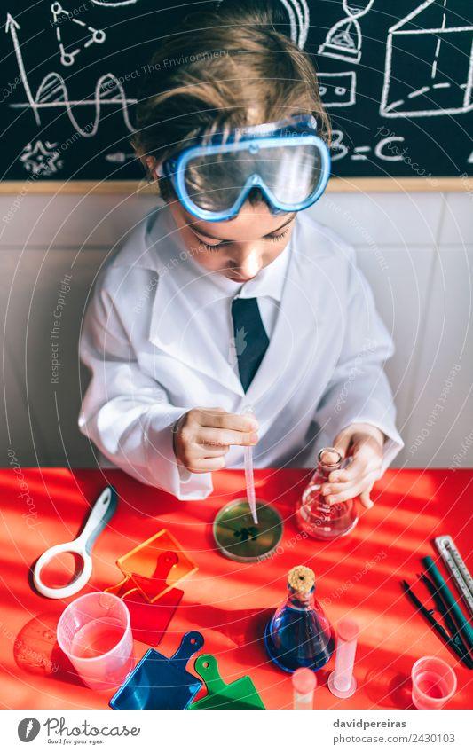 Ernsthaftes Kind beim Spielen mit chemischen Flüssigkeiten Flasche Wohnung Tisch Wissenschaften Klassenraum Labor Mensch Junge Kindheit Hand authentisch klein