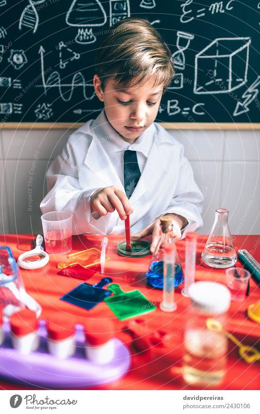 Ein Kind, das spielt, um Chemiker zu werden, mit bunten Flüssigkeiten. Flasche Löffel Glück Spielen Wohnung Tisch Wissenschaften Klassenraum Tafel Labor Mensch