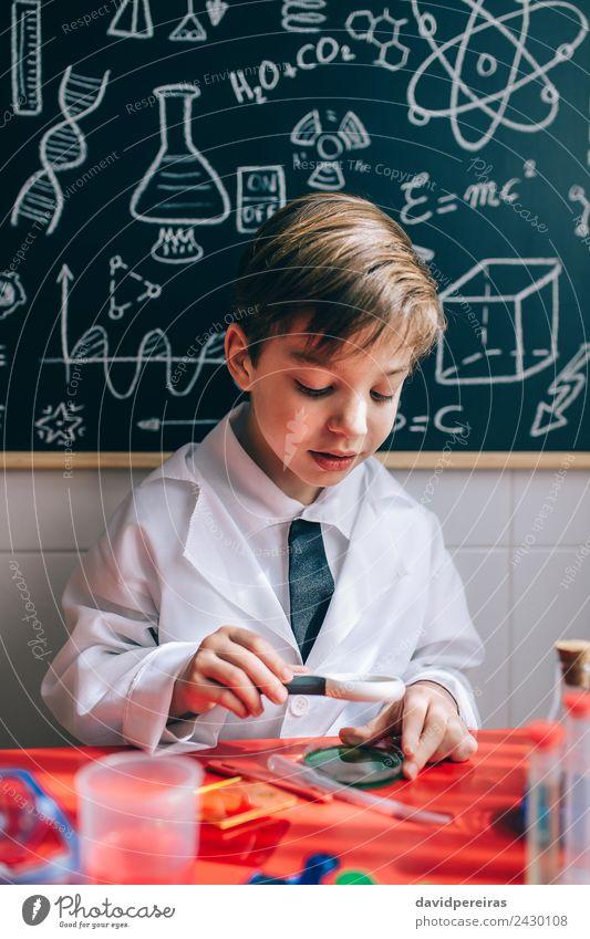 Glückliches Kind, das durch die Lupe flüssig aussieht. Flasche Freude Spielen Wohnung Tisch Wissenschaften Schule Klassenraum Tafel Labor Mensch Junge Kindheit