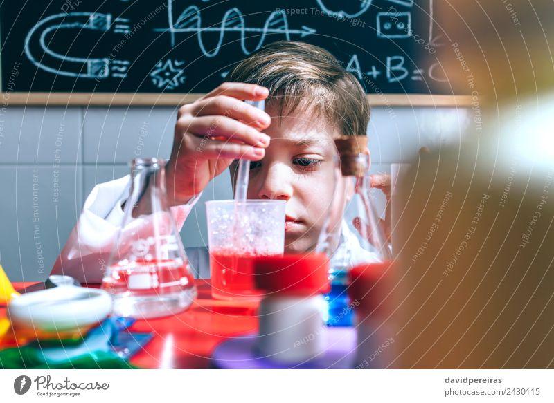 Kind spielt mit chemischen Flüssigkeiten über dem Tisch. Flasche Glück Spielen Wohnung Wissenschaften Klassenraum Tafel Labor Mensch Junge Kindheit Hand
