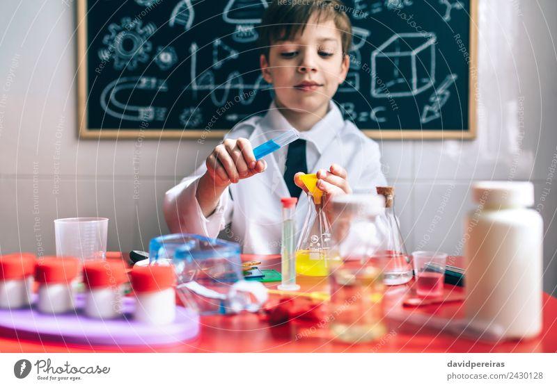 Ernsthafter kleiner Junge beim Spielen mit chemischen Flüssigkeiten Flasche Glück Wohnung Tisch Wissenschaften Kind Klassenraum Tafel Labor Mensch Kindheit Hand