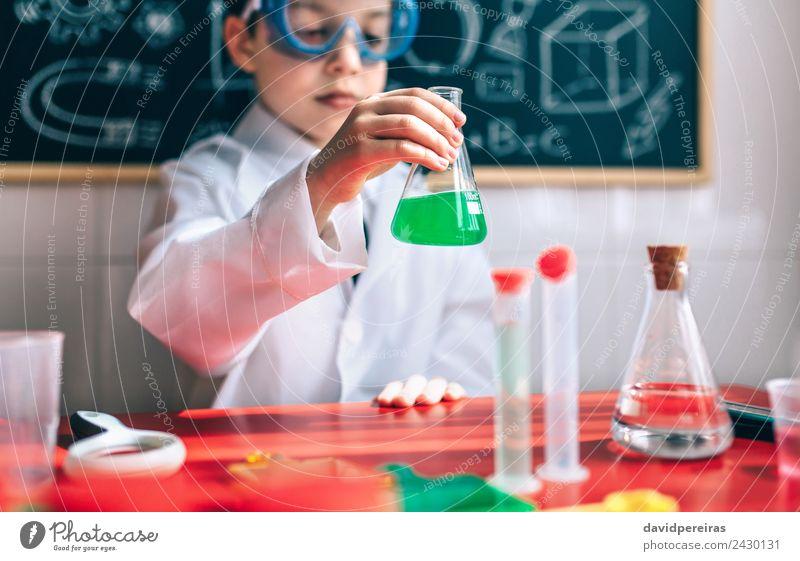 Kleiner Junge Wissenschaftler mit Brille, der eine Flasche gegen eine Tafel hält Spielen Wohnung Tisch Wissenschaften Kind Klassenraum Labor Mensch Kindheit