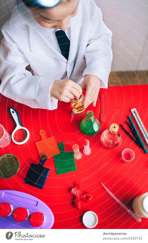 Kleiner Wissenschaftler, der Flüssigkeit in der Flasche mischt. Löffel Spielen Wohnung Tisch Wissenschaften Kind Klassenraum Labor Mensch Junge Kindheit Hand
