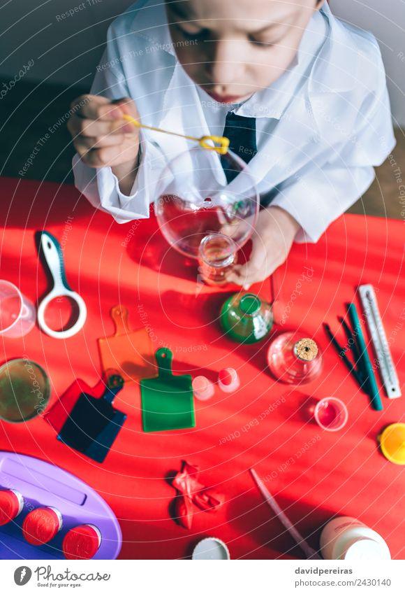 Kind macht Seifenblasen über dem roten Tisch. Flasche Freude Glück Spielen Wohnung Wissenschaften Schule Klassenraum Labor Mensch Junge Kindheit Hand