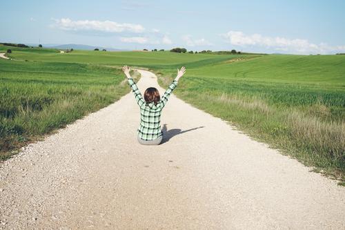 Junge Frau mit erhobenen Armen auf einem ländlichen Weg Lifestyle Design Wellness Leben harmonisch Wohlgefühl Ferien & Urlaub & Reisen Abenteuer Freiheit Sommer