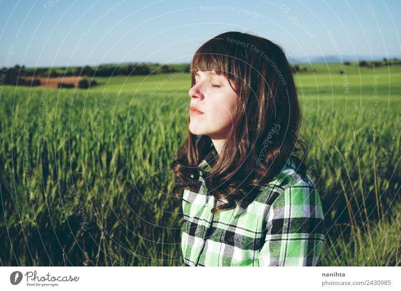 Junge Frau genießt die Sonne auf einer grünen Wiese Lifestyle schön Gesundheit harmonisch Wohlgefühl Sinnesorgane Erholung ruhig Meditation Landwirtschaft