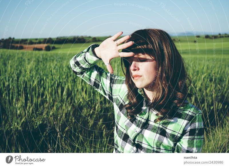 Junge Frau bedeckt ihr Gesicht vor der Sonne auf einem grünen Feld. Lifestyle Stil Gesundheit Wellness Sinnesorgane Erholung Sommer Landwirtschaft