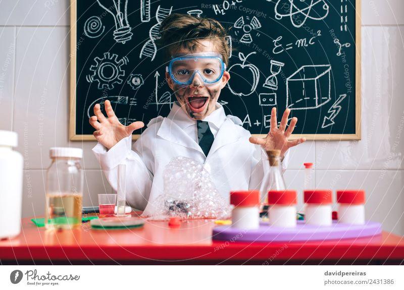 Glücklicher kleiner Junge spielt aufgeregt mit experimentellen Ergebnissen. Gesicht Spielen Wohnung Tisch Wissenschaften Kind Schule Klassenraum Tafel Labor
