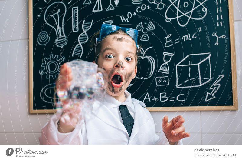 Glücklicher kleiner Junge hält Glas mit Seifenschaum. Gesicht Spielen Wohnung Tisch Wissenschaften Kind Schule Klassenraum Tafel Labor Mensch Kindheit
